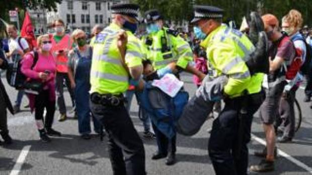An activist from the climate protest group Extinction Rebellion is carried away by police officers