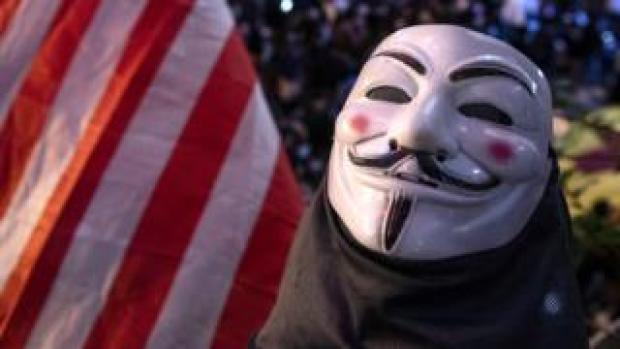 An Anonymous mask is seen next to a US flag in this photograph, which was actually taken in Hong Kong during the pro-democracy protest there in 2019