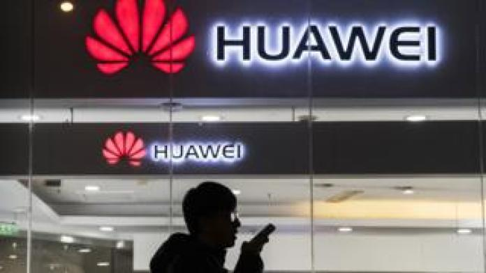 Person stands in front of Huawei logo