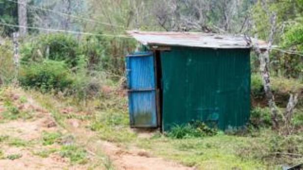 a corrugated tin outhouse