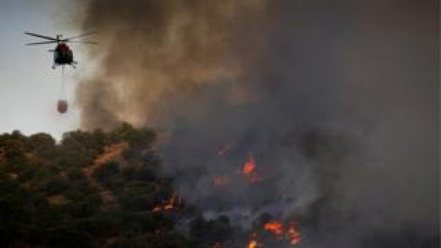 A helicopter flies over a wildfire near the city of Toledo