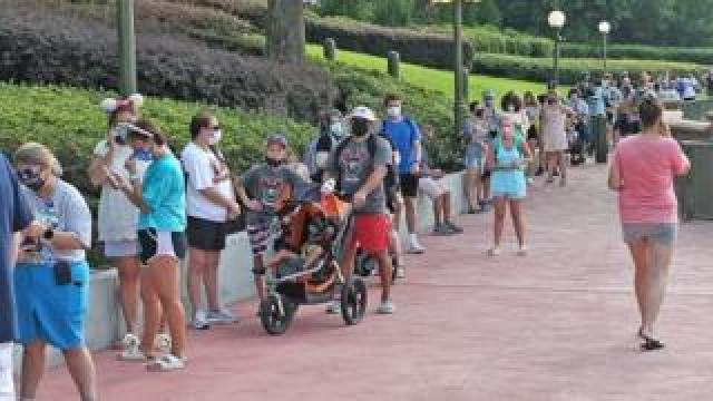 People queue outside Disney's Magic Kingdom