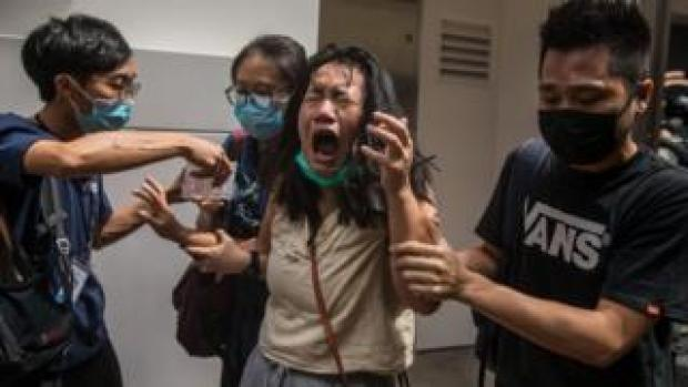 A woman hit with pepper spray during protests in Hong Kong on Wednesday