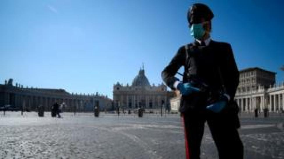 trump An armed police officer, wearing a face mask, patrols a closed and deserted St Peter's Square in the Vatican
