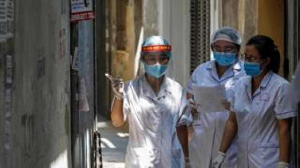 Healthcare workers are seen at a lane near the house of a COVID-19 patient as they investigate infection links in Hanoi
