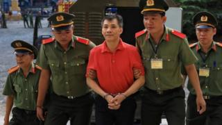 Michael Phuong Minh Nguyen (centre) is escorted by Vietnamese police to a court in Ho Chi Minh. Photo: 24 June 2019