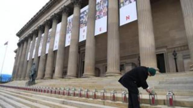 A man lights 96 lanterns arranged on the steps of St George's Hall in Liverpool