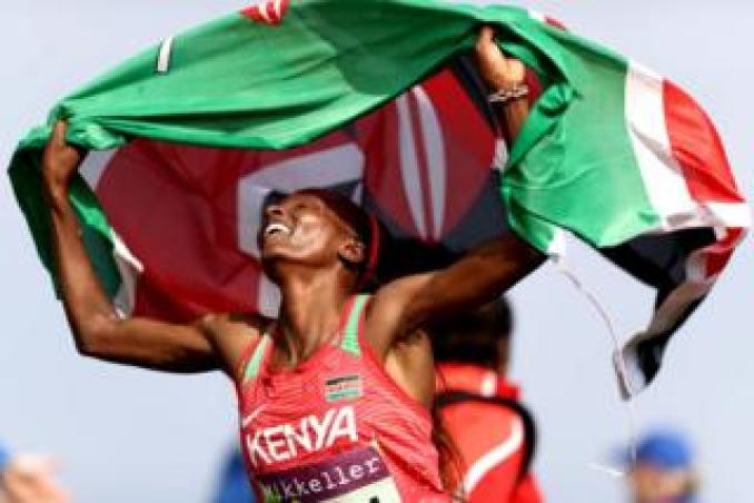 Hellen Obiri of Kenya holds the Kenyan national flag above her head and smiles moments after winning the Women's Senior Final during the IAAF World Athletics Cross Country Championships on 30 March 2019 in Aarhus, Denmark