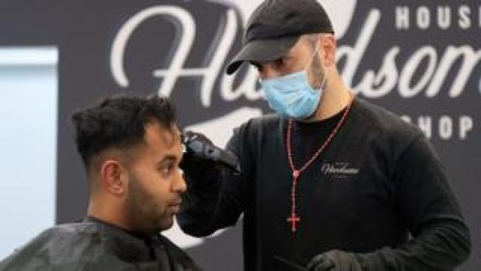 A barber wearing a face mask cuts a customer's hair in Wellington, New Zealand