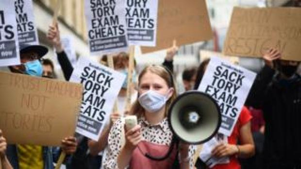 People take part in a protest outside the Department of Education in Westminster, London