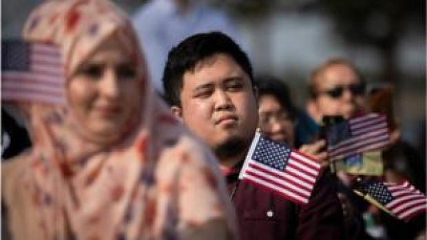 New American citizens wave American flags while 'America The Beautiful' is sung during a naturalisation ceremony