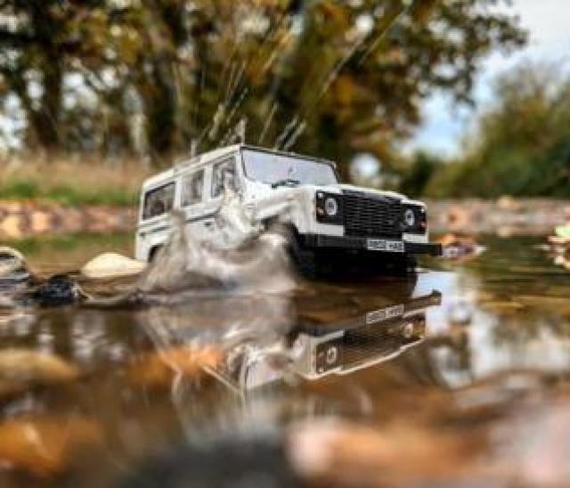 White model Land Rover splashes through puddle