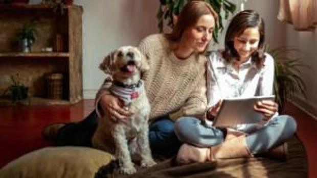 Mother, daughter and dog in front of tablet computer