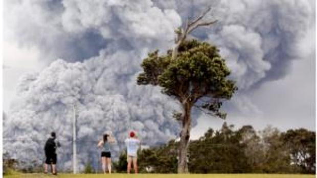 People watch as ash erupts from the Halemaumau crater near the community of Volcano during ongoing eruptions of the Kilauea Volcano in Hawaii, U.S., May 15, 2018