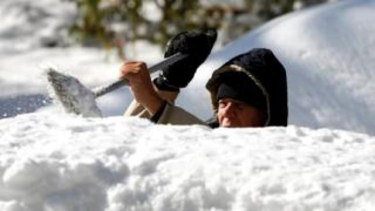 A man cleans the snow from the top of his vehicle in Detroit, Michigan, 12 November, 2019