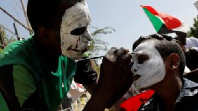 demonstrator helps paint another one's face