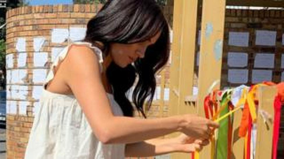The Duchess of Sussex ties a ribbon at a memorial to murdered student Uyinene Mrwetyana in South Africa