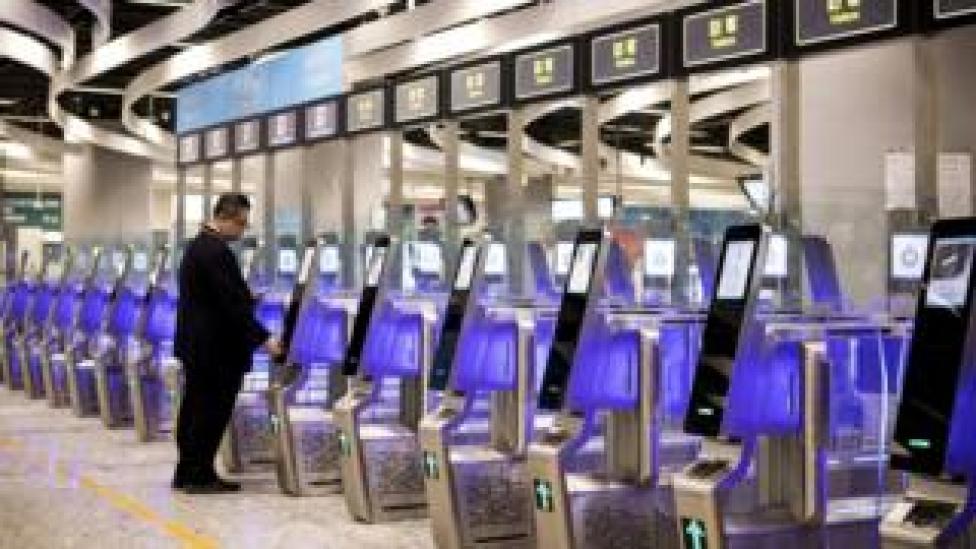 Un hombre usa una máquina de despacho de inmigración en el Hong Kong Express Rail Link