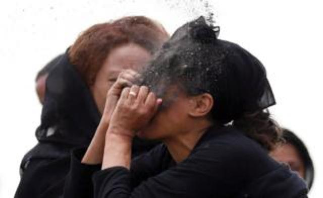 A woman puts soil on her face as she mourns at the scene of the Ethiopian Airlines Flight ET 302 plane crash
