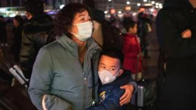 A Chinese boy hugs a relative as she leaves to board a train at Beijing Railway station before the annual Spring Festival