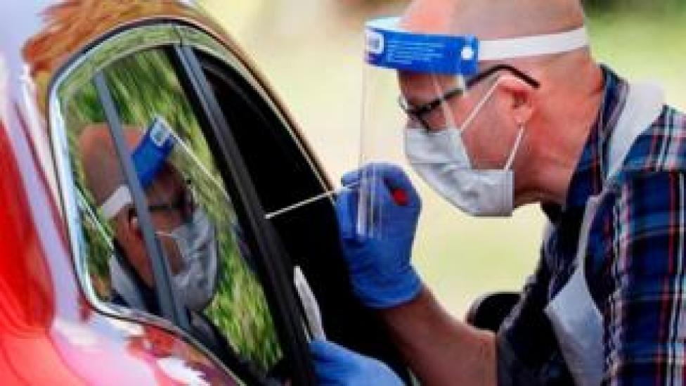 A man holding a swab takes a a test from someone in a car.