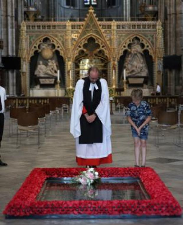 The Reverend Canon Anthony Ball with Toby Wright, son of the Reverend Paul Wright, sub-dean of the Chapel Royal, who brought Princess Beatrice's bouquet from the wedding to be placed on the tomb of the unknown warrior