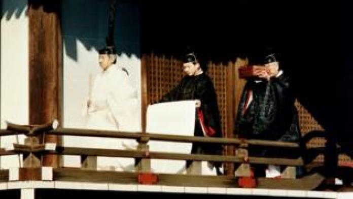 Emperor Akihito accompanied by Shinto priests carrying an imperial treasure in the palace (1990)