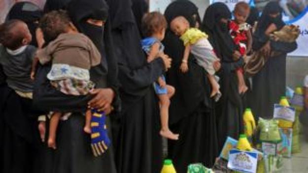 Yemeni women and children wait during food distribution in the province of Hodeida, Yemen, on 30 May 2018