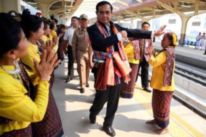 Thailand's Prime Minister Prayuth Chan-ocha performs a traditional dance with performers at Khon Kaen railway station
