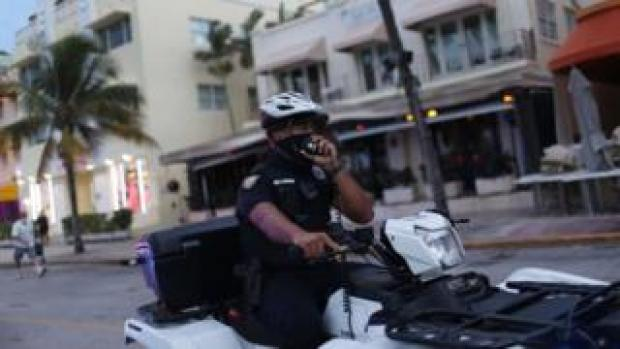 A Miami police officer wears a mask to enforce the city's mask mandate