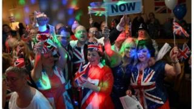 """Brexit supporters wave Union flags as the time passes 11 O""""Clock at a Brexit Celebration party at Woolston Social Club in Warrington, north west England"""