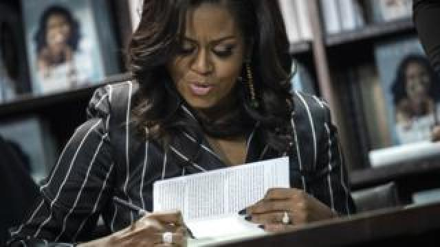 """Former US First Lady Michelle Obama signs copies of her new book """"Becoming"""" at a Barnes and Noble bookstore in New York City, 30 November 2018"""