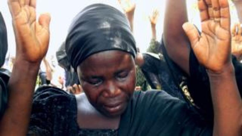 Bintu Bitrus, the mother of Godiya, one of the missing Chibok schoolgirls, weeps as she raises her hands along with other parents to pray for the release of their daughters kidnapped by Boko Haram jihadists, during a worship service to mark the fourth anniversay of the kidnapping at Chibok Town, Borno State, on April 14, 2018