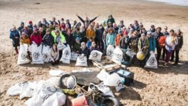 A group of volunteers cleaning up a beach in Cornwall for Surfers Against Sewage