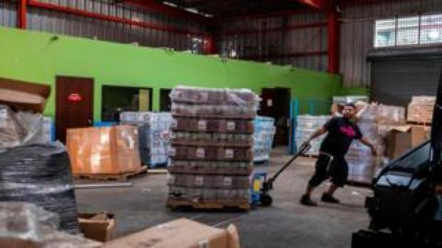 A man pulls a pallet of gas canisters in a warehouse in Ponce, Puerto Rico on January 18, 2020