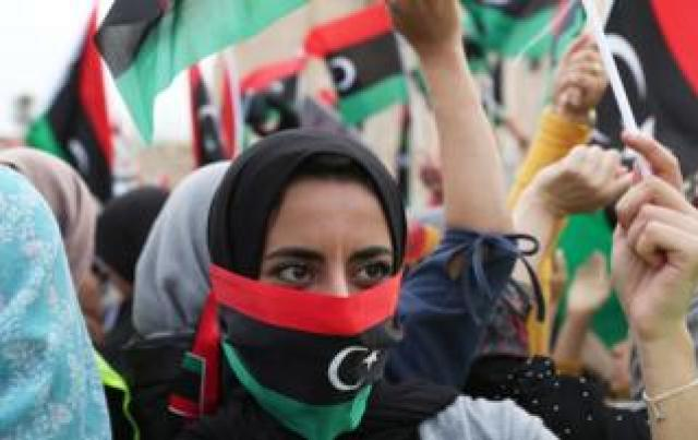 """A Libyan woman covers her face with Libyan flag as she attends a demonstration to demand an end to the Khalifa Haftar""""s offensive against Tripoli, in Martyrs"""" Square in central Tripoli, Libya April 26, 2019"""