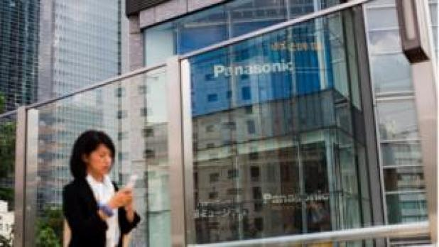 A woman walks past a Panasonic building in Tokyo on May 11, 2017.