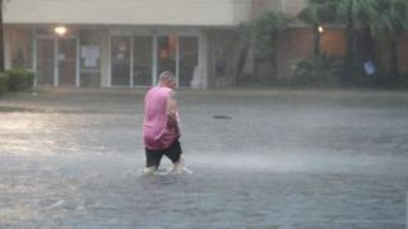 A man wades through a flooded car park in Gulf Shores, Alabama