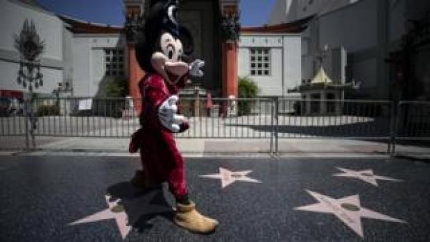An entertainer wearing a Mickey Mouse costume in front of the closed Chinese TLC Theater on the almost empty Hollywood Boulevard