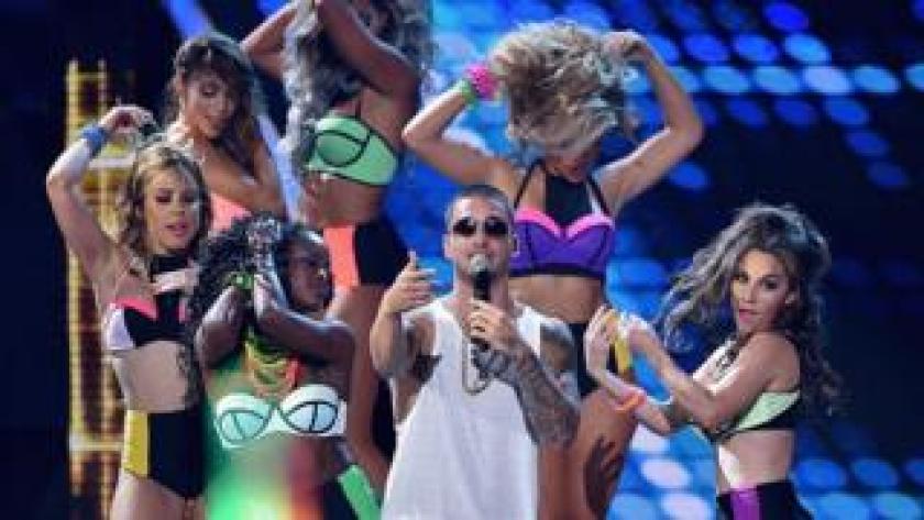Maluma en un concierto rodeado de mujeres.