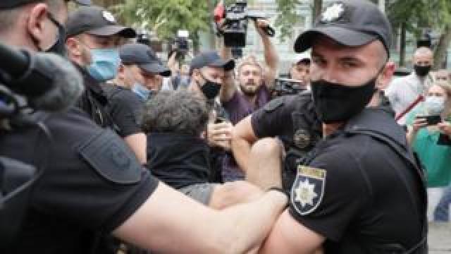 Ukrainian policemen detain a man during protests