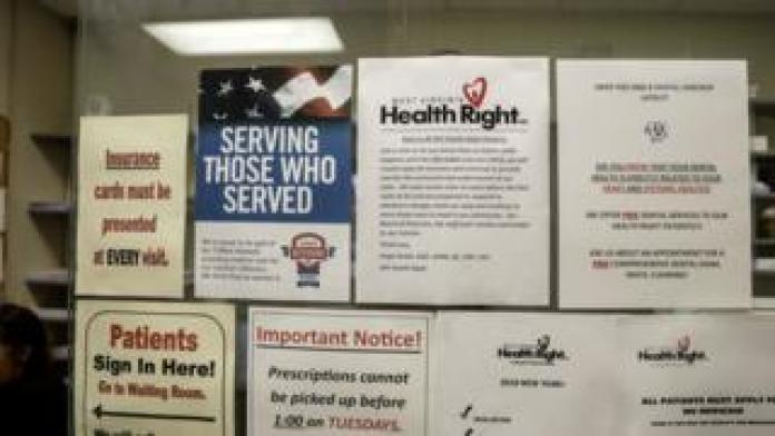 Flyers at front desk of clinic discussing insurance, veterans, affordable care act