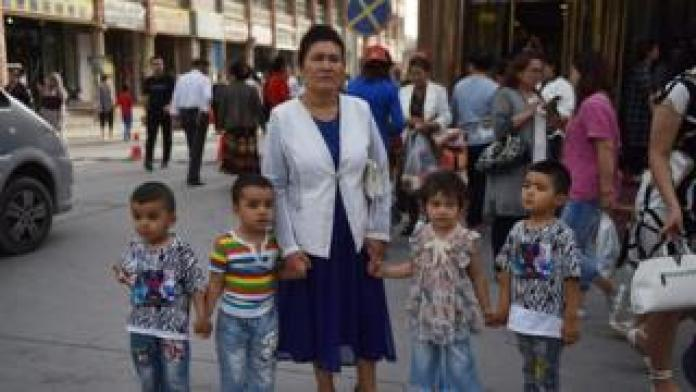 This file photo taken on June 4, 2019 shows a Uighur woman waiting with children on a street in Kashgar in China's northwest Xinjiang region.