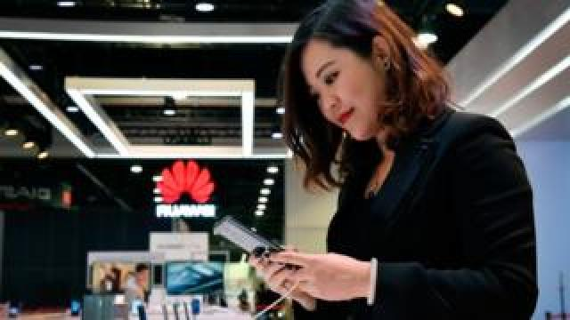 Woman looking at Huawei phone