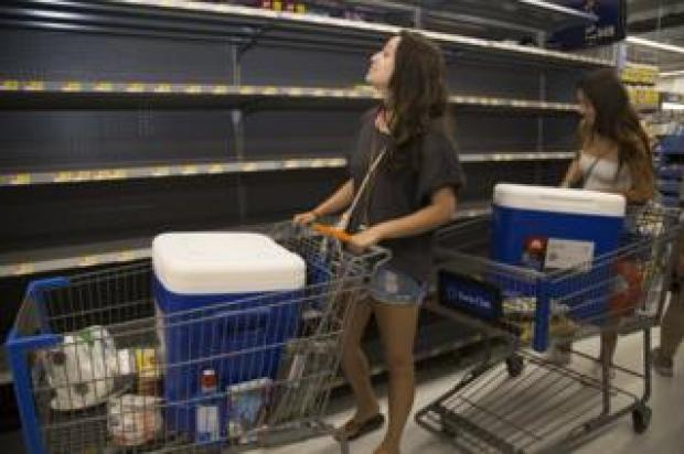 University of Hawaii at Manoa students push trolleys around a supermarket.