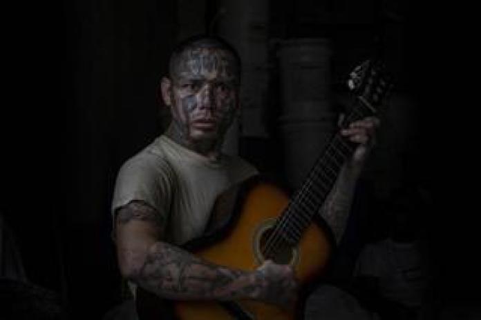 An inmate and former member of the La 18 gang plays guitar at Penal San Francisco Gótera, El Salvador. November 8, 2018.