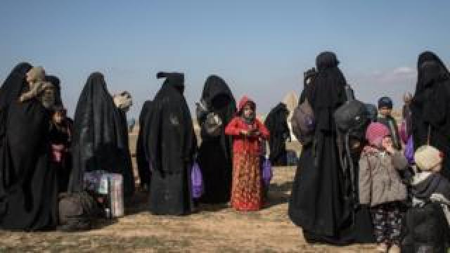 Civilians who have fled fighting in Baghuz wait to board trucks after being screened by members of the Syrian Democratic Forces (SDF) on February 9
