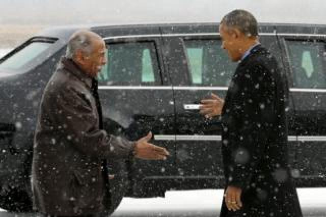 John Conyers (D-MI) (L) greets President Barack Obama as he arrives aboard Air Force One at Detroit Metropolitan Wayne County Airport in Detroit, Michigan January 20, 2016.