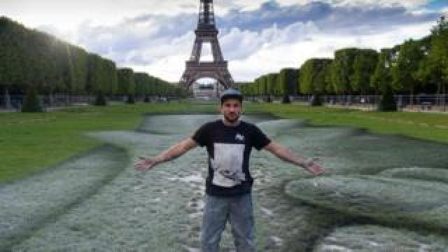 """French street artist Saype poses at the Eiffel Tower in front of his giant artwork """"Beyond Walls"""""""
