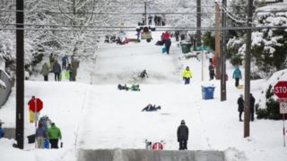 People sledge down a road